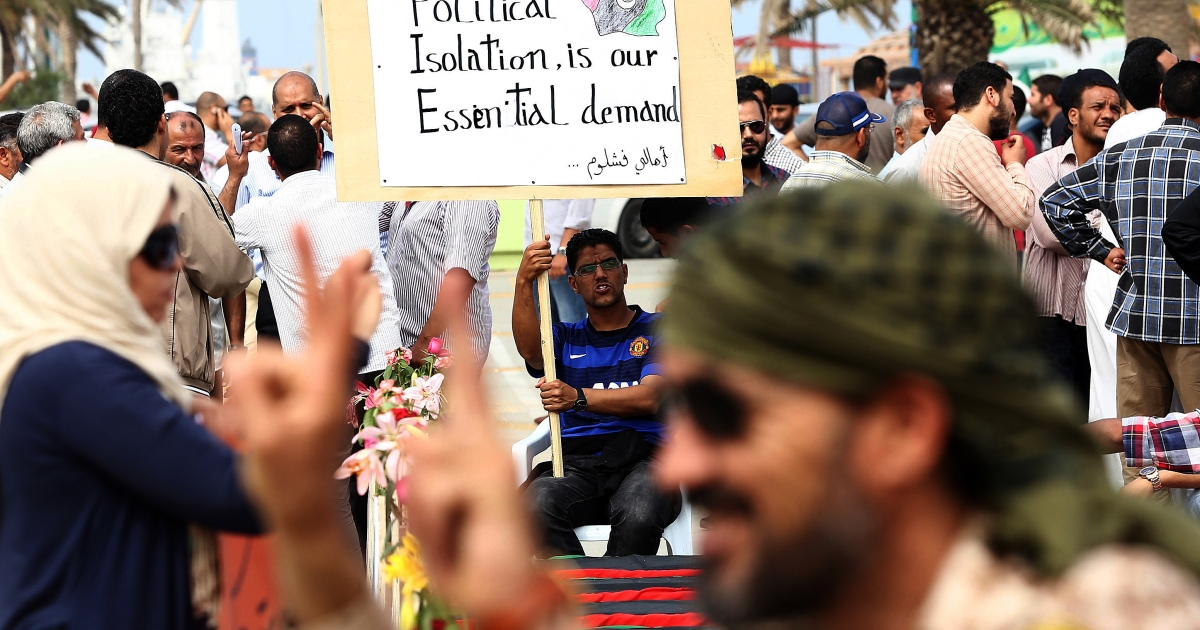 Libyan protesters hold placards and banners during a demonstration in support of the Political Isolation Law in Libya's landmark Martyrs Square' on May 5, 2013 in Tripoli, Libya. Libya's General National Congress, under pressure from armed militias, voted through a controversial law to exclude former regime officials from government posts. Gunmen who had surrounded the foreign and justice ministries lifted the sieges when state television broke the news.</p>