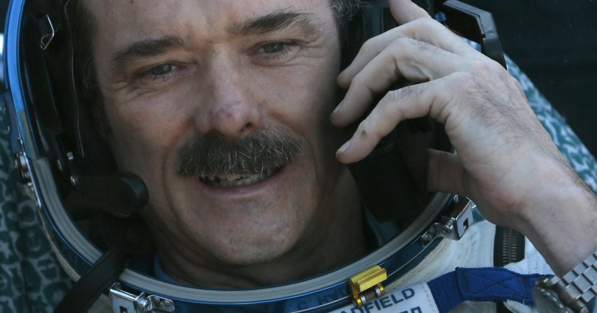 Canadian astronaut Chris Hadfield speaks on the phone shortly after the landing aboard the Russian Soyuz space capsule some 90 miles southeast of the town of Zhezkazgan in central Kazakhstan on May 14, 2013.</p>