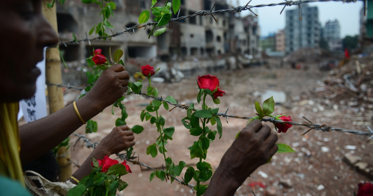 A Bangladeshi family member of a missing garment worker places roses on the barbed wire fence as she pays tribute to the victims at the site of the April 2013 collapse in Savar, on the outskirts of Dhaka on May 24, 2013. Industrial disasters since November have killed at least 1,250 workers, highlighting the appalling safety problems in the plants where three million workers toil for a basic monthly wages of $40, among the world's lowest.</p>