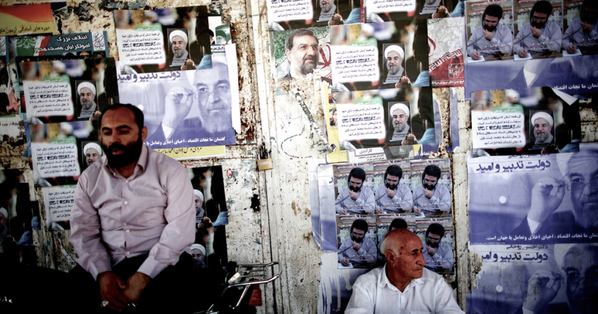 Iranians sit next to electoral posters of Hassan Rowhani (L) and Mohsen Rezai (C) in the religious city of Qom some 130 kilometres south of the capital on June 9, 2013.</p>