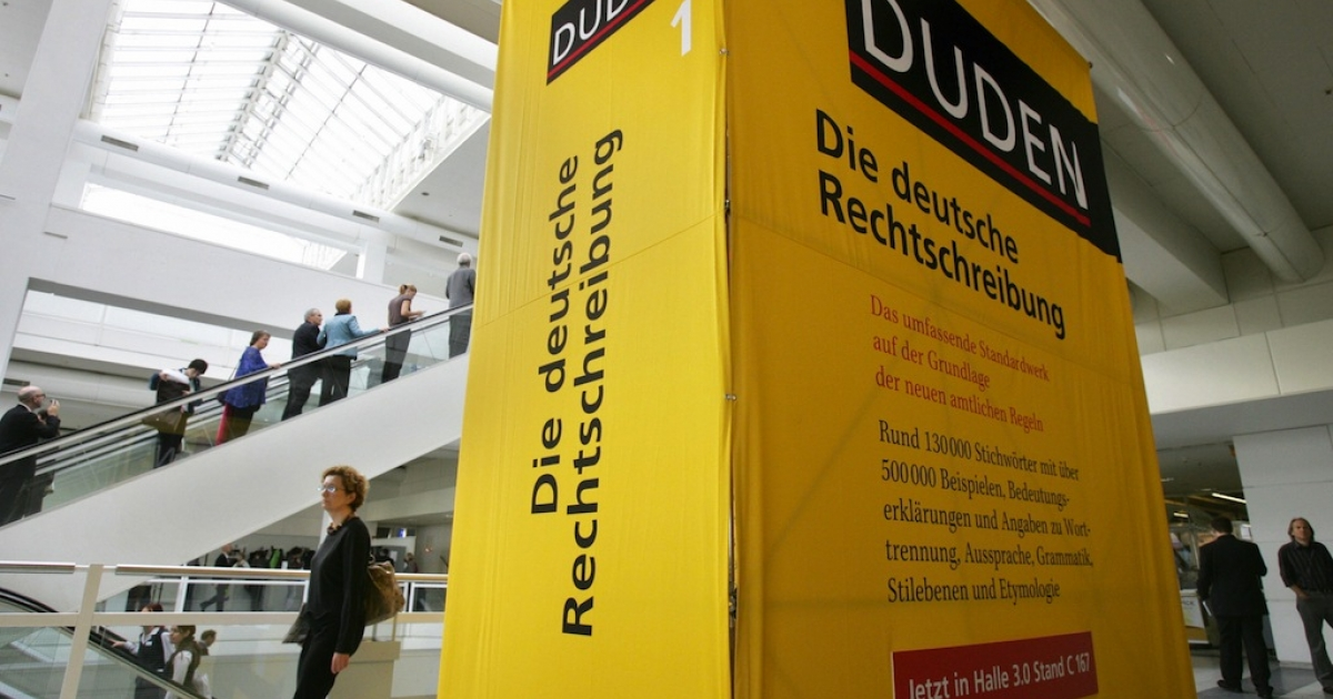 Fair-goers walk past an oversized Duden dictionary of 'Correct German Spelling' at the international Frankfurt Book Fair October 4, 2006. (JOHN MACDOUGALL/AFP/Getty Images)</p>