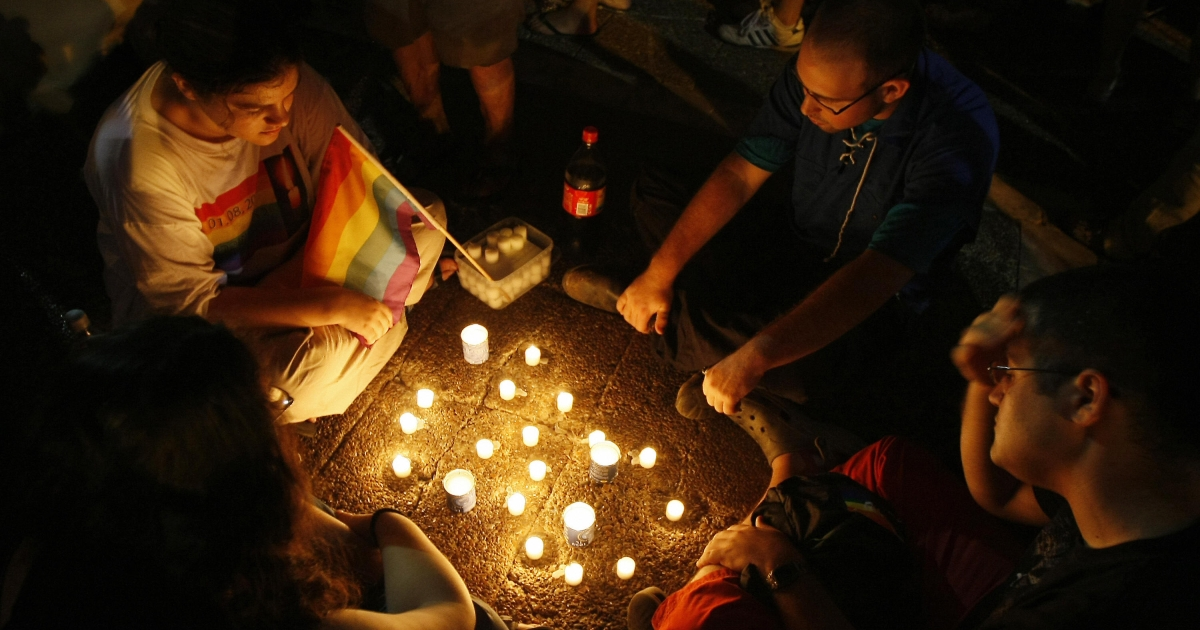 Israelis sit around lit candles during a mass rally of solidarity with the victims of an attack on a gay center, in Tel Aviv's Rabin Square on August 8, 2009.</p>