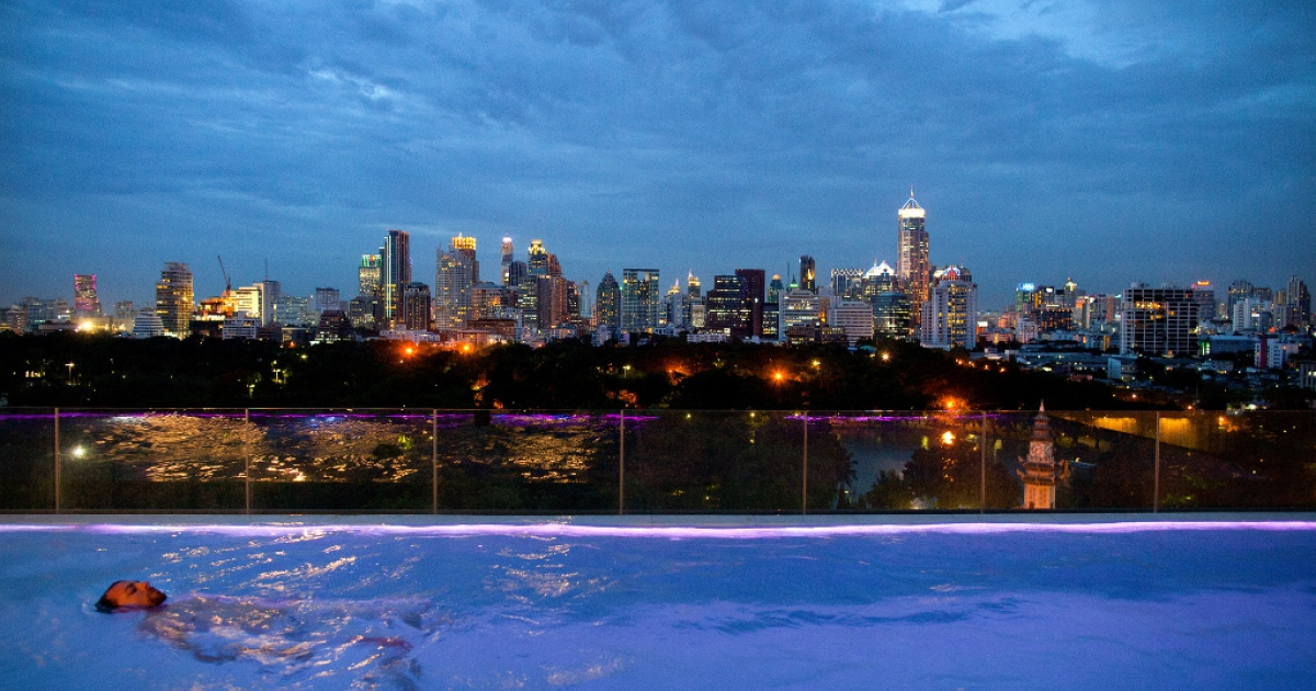 A man swims at dusk in the infinity pool at the new Sofitel hotel June 20, 2012 in Bangkok.</p>