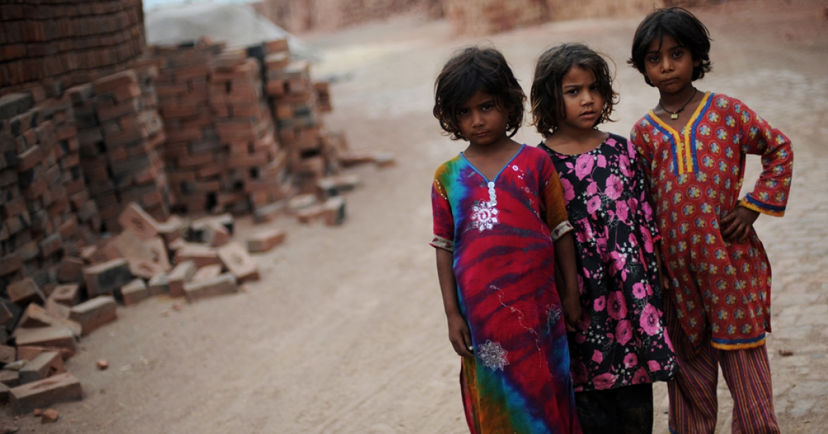 Sana, from left, Farzna and Sama stand near piles of bricks at a kiln near Lahore, Pakistan on July 6, 2012. According to the International Labor Organization, there are 10.5 million children worldwide working as domestic laborers.</p>
