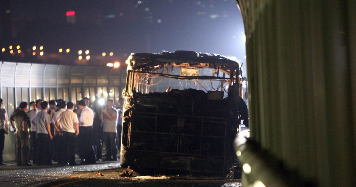 This picture taken on June 7, 2013 shows investigators at the scene of a bus that caught fire on the BRT (Bus Rapid Transit) elevated road in the city of Xiamen, China's southeast Fujian province.  A fire that engulfed a commuter bus in minutes during rush hour in the Chinese city of Xiamen, killing 47 and injuring dozens more, appears to have been deliberately set, state media quoted investigators as saying on June 8.</p>