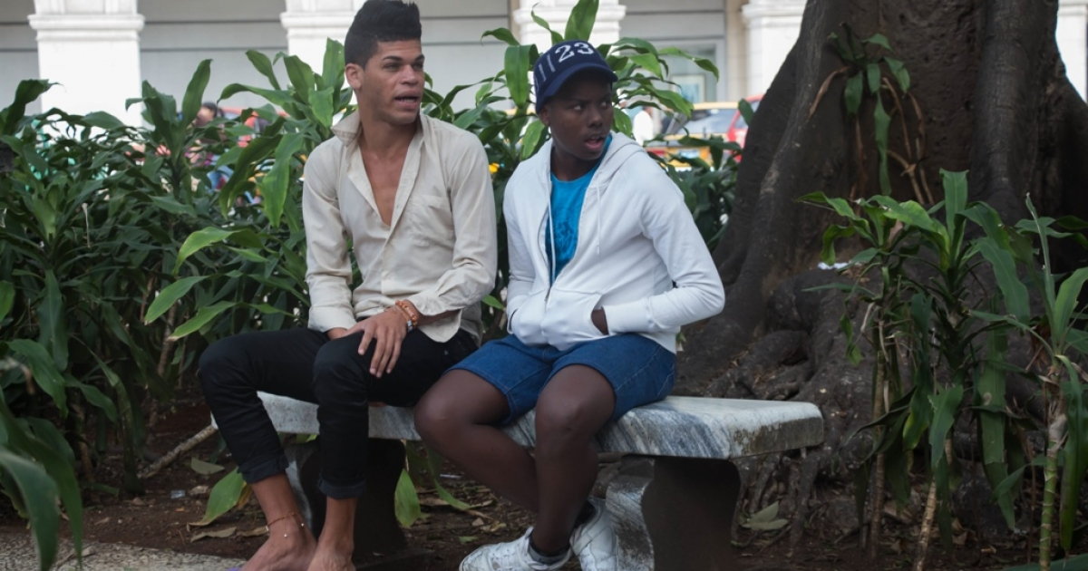 Two Cuban men sit in Havana's Central Park, waiting for customers.</p>