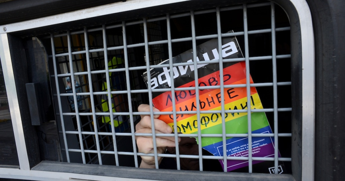 A Russian LGBT rights activist holds a sign reading 'Love is stronger than homophobia' from inside a Russian riot police van, during an unauthorized gay rights rally in central Moscow on May 25, 2013.</p>