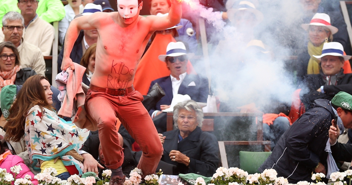 A protester runs onto court with a lit flare before the start of a game in the men's final between Rafael Nadal of Spain and David Ferrer of Spain at the French Open on June 9, 2013 in Paris.</p>