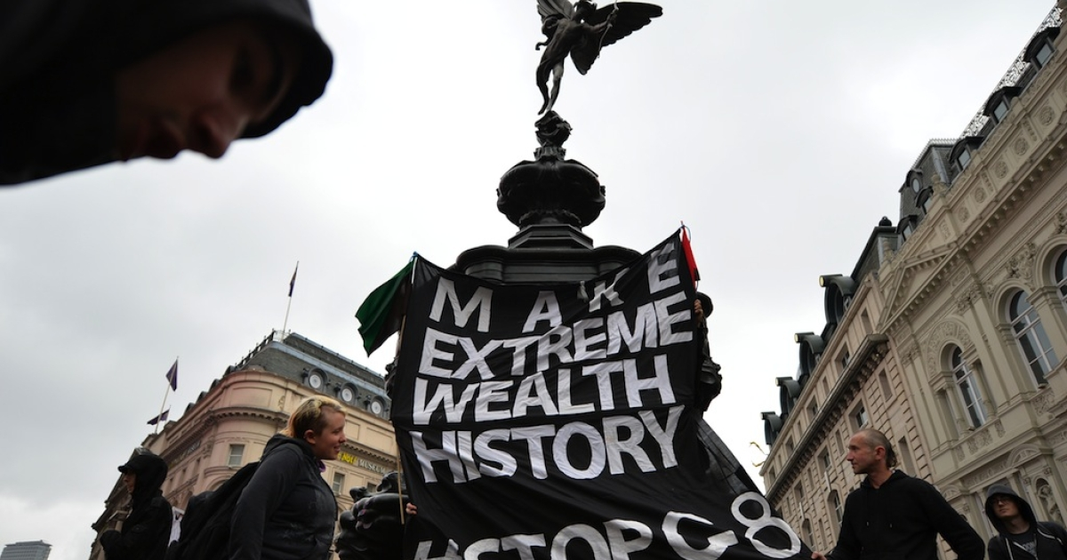 Anti-capitalist protesters hang a banner underneath the statue of Eros in Piccadilly Circus in central London on June 11, 2013.</p>