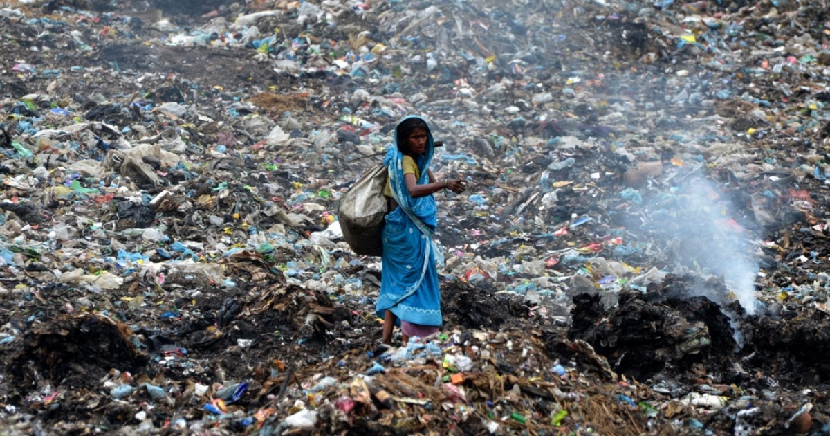 An Indian ragpicker walks among heaps of rubbish at a municipal waste dump in Dimapur on April 22, 2013, on World Earth Day.</p>