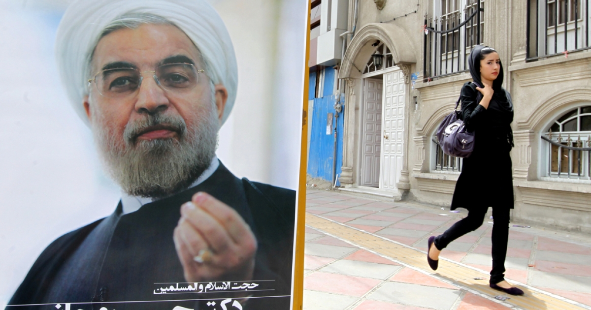 An Iranian woman walks past a campaign poster of Hassan Rowhani, moderate presidential candidate and former top nuclear negotiator, in Tehran on June 11, 2013.</p>