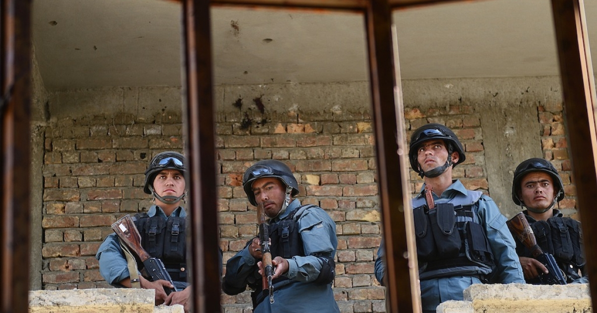 Afghanistan policemen stand guard in a building which was used for attack on Kabul airport on June 10, 2013. All seven militants who launched the died in the assault, Afghan police said.</p>