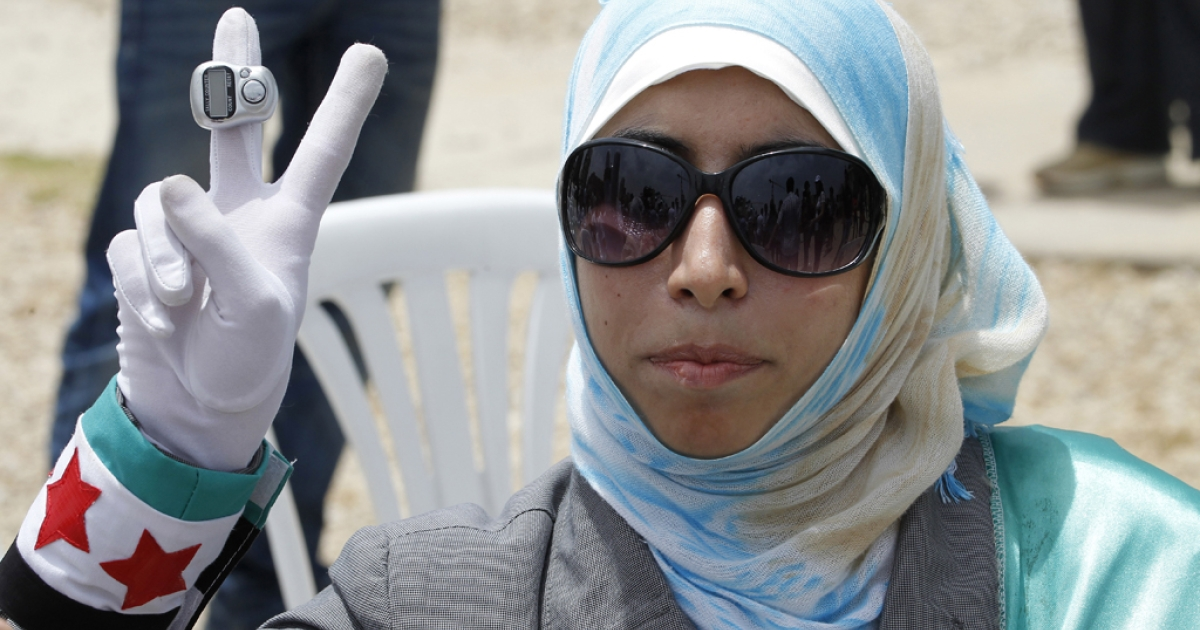 A Lebanese woman flashes a peace sign during a protest against Hezbollah on June 9, 2013, in the Lebanese capital, Beirut.</p>