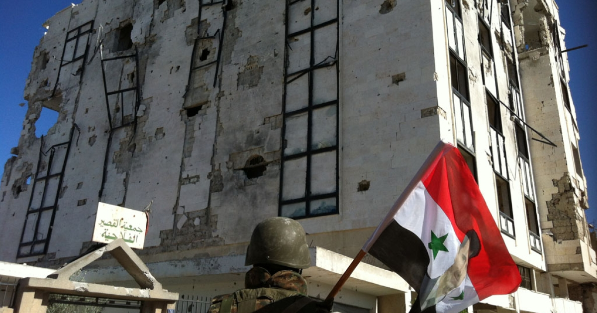 A Syrian army's soldier a flag featuring Syria's President Bashar al-Assad in front of a building left in ruins in the city of Qusayr on June 5.</p>