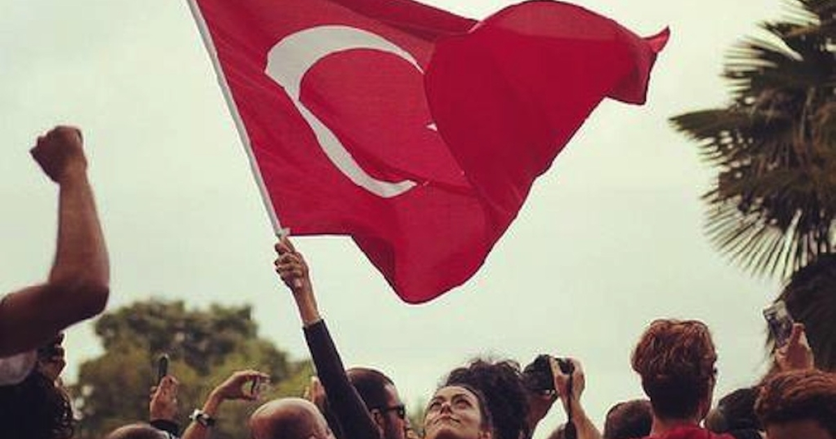 A protester waves a Turkish flag.</p>
