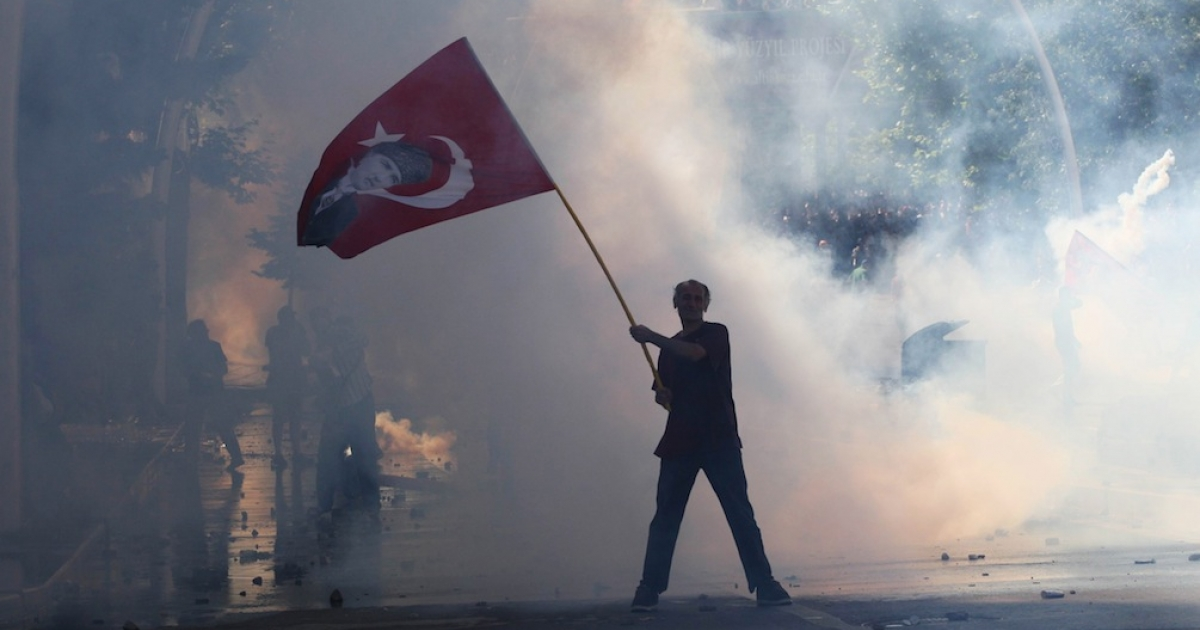 Tear gas surrounds a protestor holding a Turkish flag with a portrait of the founder of modern Turkey Mustafa Kemal Ataturk as he takes part in a demonstration in support of protests in Istanbul and against the Turkish Prime Minister and his ruling Justice and Development Party (AKP), in Ankara, on June 1, 2013.</p>
