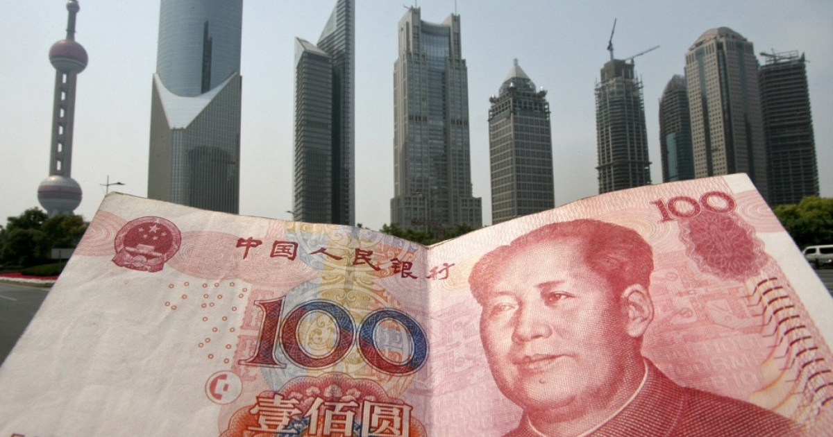 Shanghai, CHINA: A Chinese 100 renminbi (yuan) note is held up in front of the Pudong financial district skyline in Shanghai, 21 May 2007.</p>