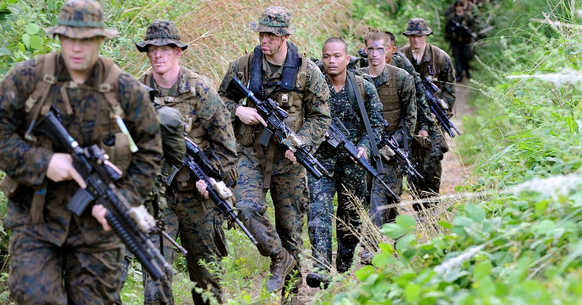 US Marines and their Philippine counterparts inspect a hill during joint military training exercises in Cavite, south of Manila on October 11, 2010.</p>