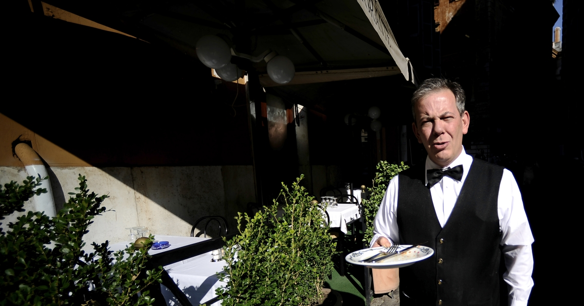 A waiter carries a plate in front of a restaurant in downtown Rome in November 2011.</p>