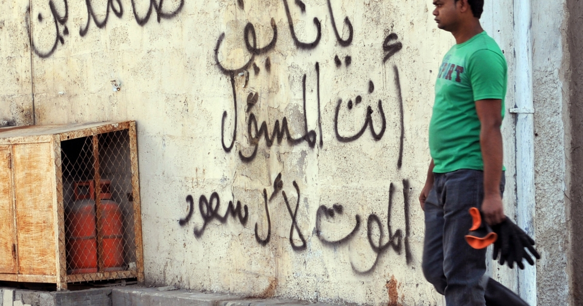 A foreign worker walks past graffiti against the ruling Saudi royal family in the mostly Shia Qatif region of Eastern Province on November 25, 2011. Four people have been killed and nine others wounded in an exchange of gunfire between security forces and what the Saudi interior ministry called criminals serving a foreign power in the country's oil-producing Eastern Province.</p>