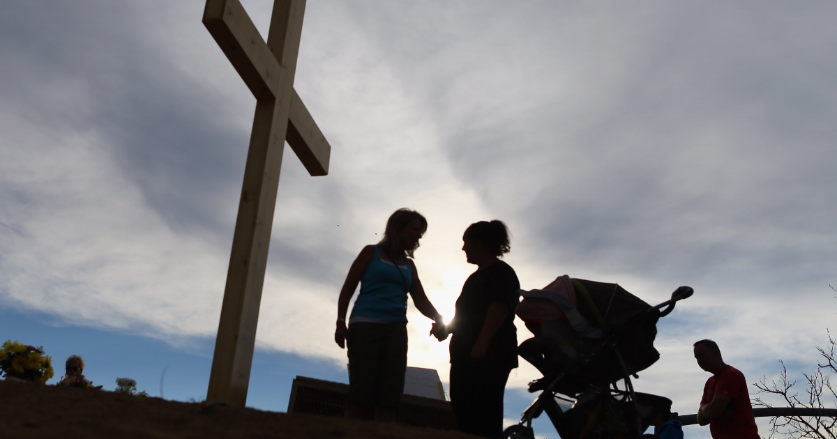 People pray together near a cross erected in a memorial setup across the street from the Century 16 movie theatre on July 30, 2012 in Aurora, Colorado.</p>