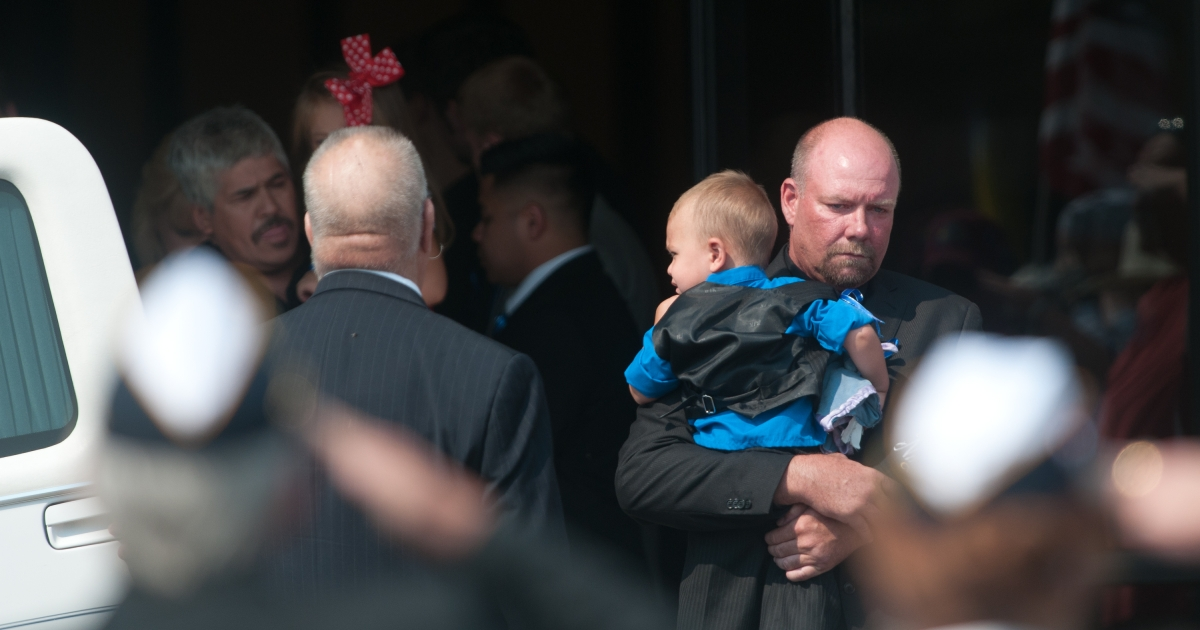 Randy Blunk, father of Aurora, Colorado shooting victim Jonathan Blunk, leaves Mountain View Mortuary with his grandson Maximus following his son's service August 3, 2012 in Reno, Nevada.</p>