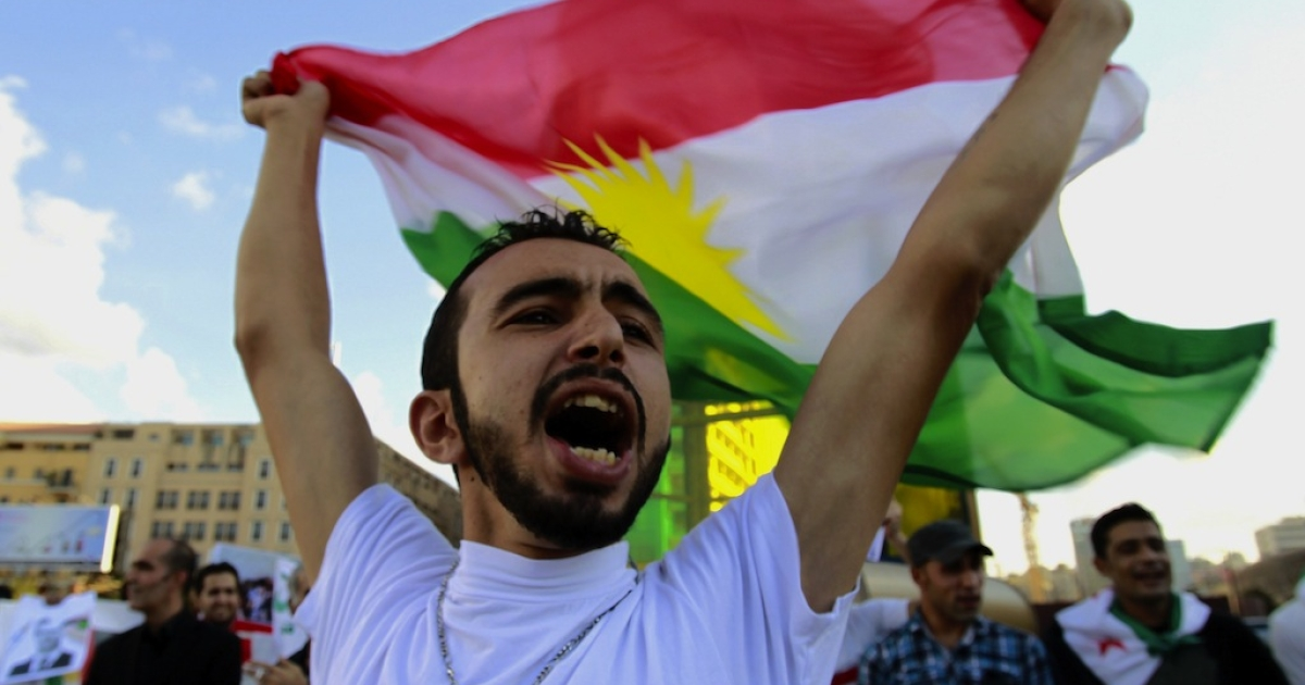 A Syrian Kurd residing in Lebanon holds up a Kurdish flag during a protest in Beirut on Oct. 7, 2012 to mark the first anniversary of the assassination of the Syrian Kurdish opposition leader, Meshaal Tamo.</p>
