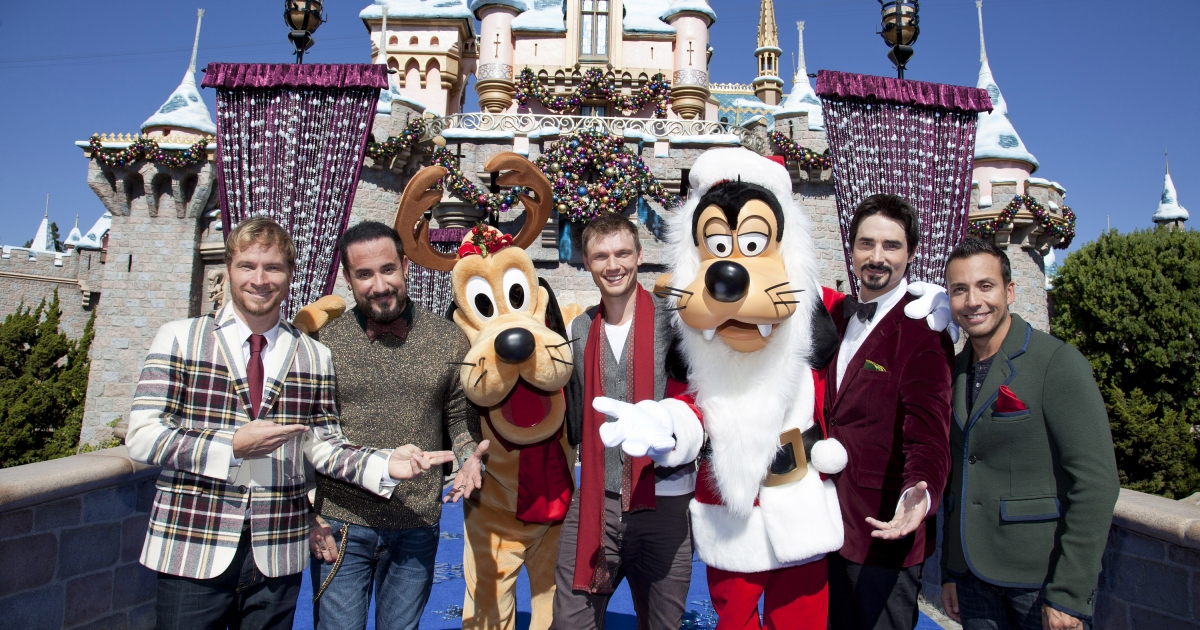 Backstreet Boys pose Nov. 4, 2012 with Santa Goofy and Pluto in front of Sleeping Beauty Castle at Disneyland Park in Anaheim, California.</p>