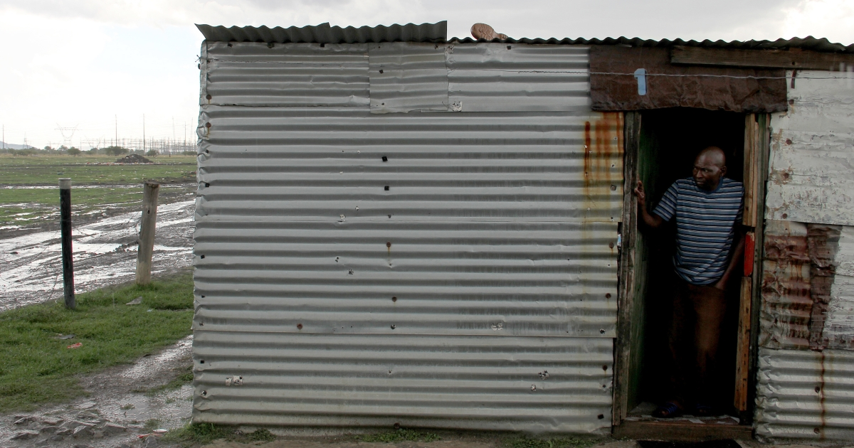A mineworker stands on his doorstep on October 30, 2012 at Nkaneng informal settlement near the Lonmin platinum mine in Marikana, northwest of Johannesburg. The squalid living conditions for miners were among the reasons for the bloody strike at Marikana, 70 miles northwest of Johannesburg. Mehlwana's hut is the largest of a dozen structures erected around a mucky courtyard. There are two communal toilets and a water tap for the more than 30 inhabitants.</p>