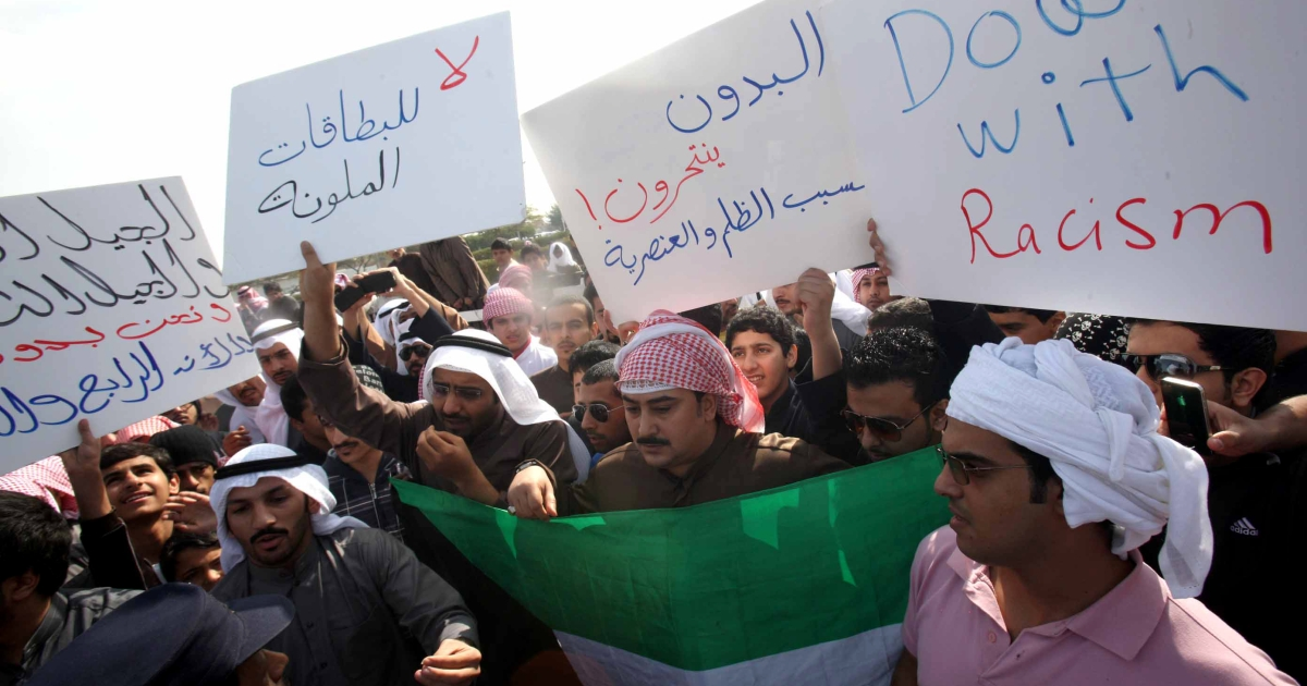Stateless Arabs, locally known as bidoons, hold signs demanding Kuwaiti citizenship and calling for an end to racism and injustice during a demonstration in January 2013.</p>