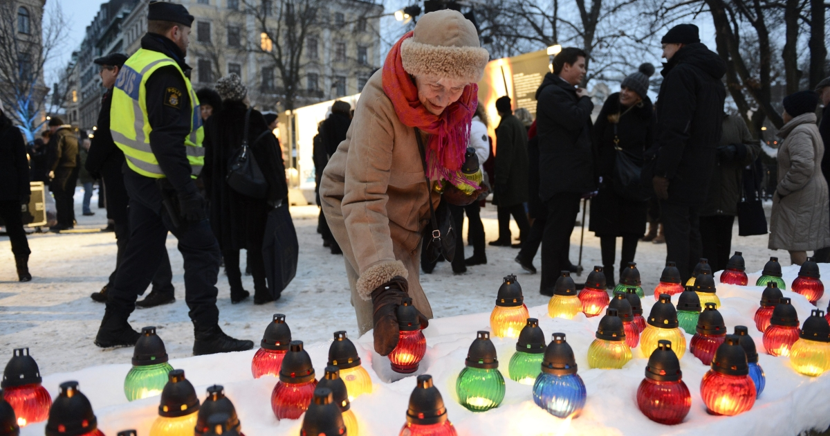 A woman lights a candle as she attends a memorial ceremony during the International Holocaust Remembrance Day on January 27, 2013, at Raoul Wallenberg Square in Stockholm, Sweden.</p>