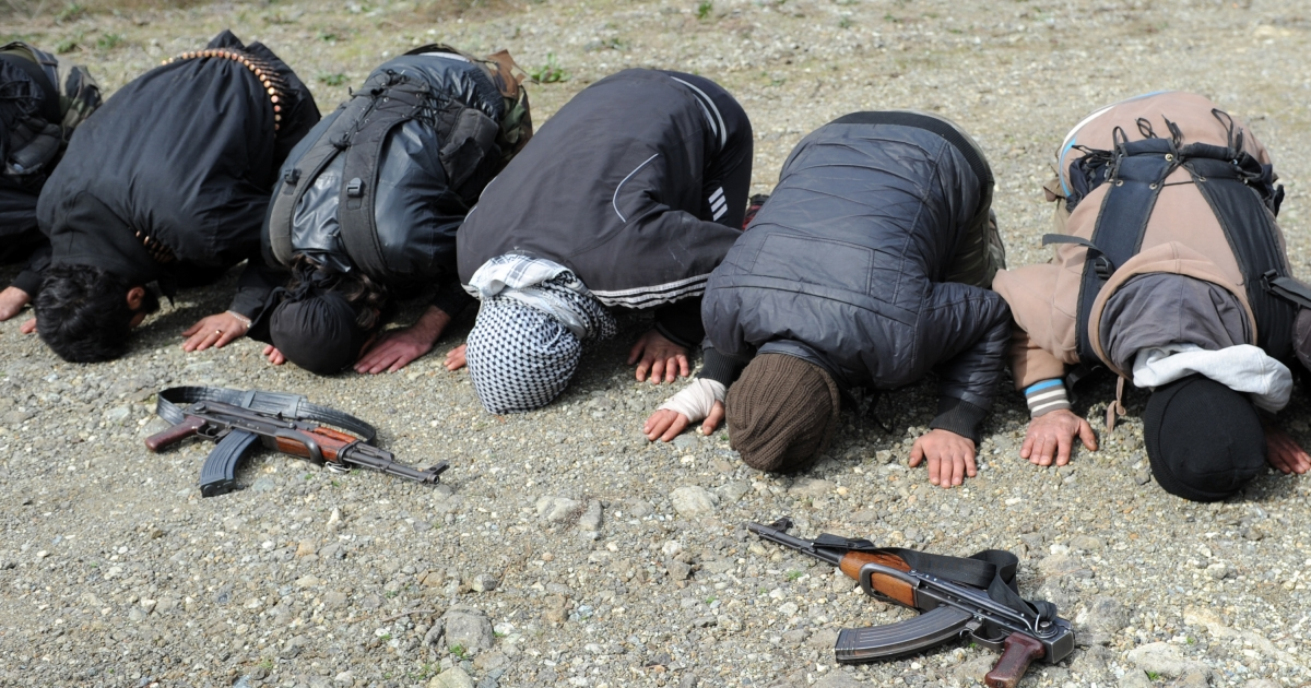 Rebel fighters offer prayers near their position as they prepare to fight against pro-Syrian regime forces on the Jabal al-Turkman mountains in Syria's northern Latakia province, on February 5, 2013.</p>
