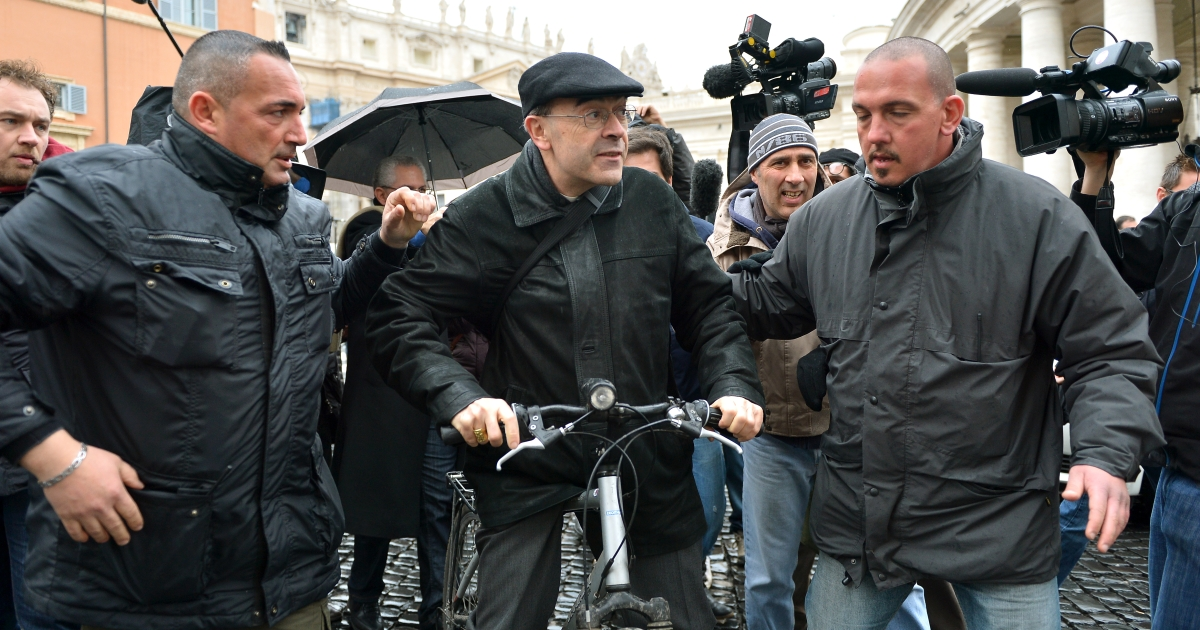 French cardinal Philippe Barbarin (C) is escorted by security as journalists surround him when leaving on his bicycle after a pre-conclave meeting on March 6, 2013 at the Vatican. The Vatican on Wednesday said no date had been set for a conclave to elect a new pope and that not all the 115 'cardinal electors' expected to take part in the vote had arrived yet.</p>