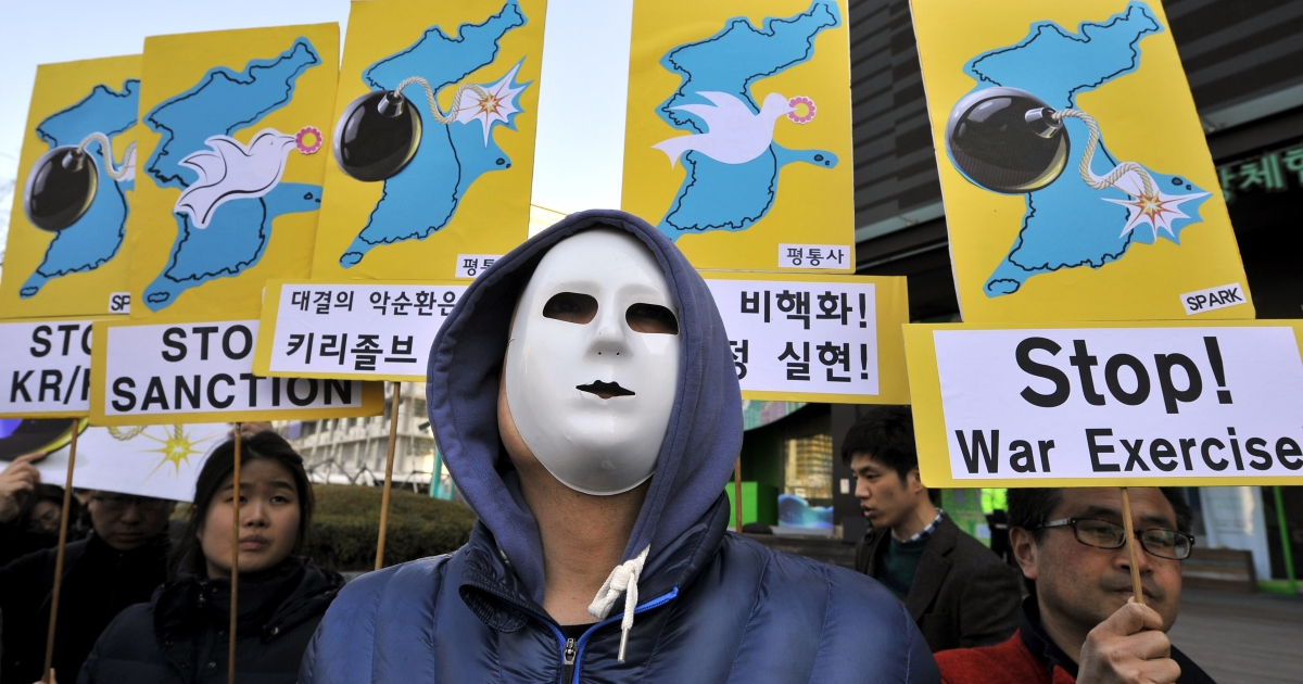 Anti-war activists wearing masks hold placards showing the Korean Peninsula during a protest against a joint military exercise between South Korea and the US, called Key Resolve, near the US embassy in Seoul on March 11, 2013.</p>