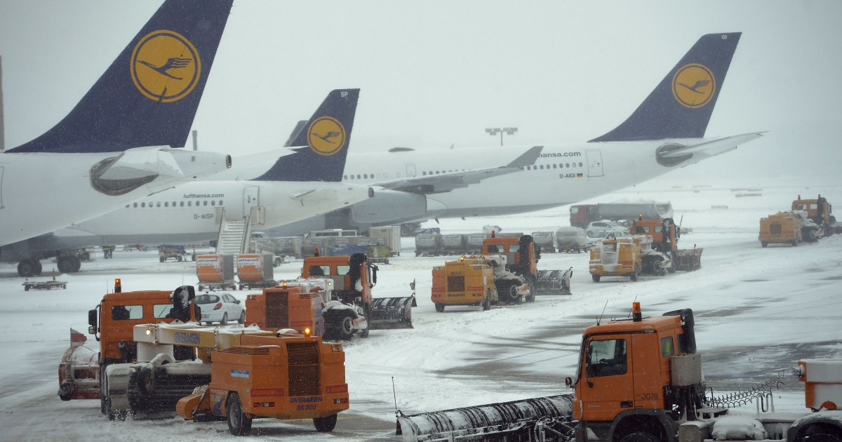 Snow plows pass Lufthansa airplanes on there way to the runway at Frankfurt International Airport on March 12, 2013 in Frankfurt am Main, Germany.</p>