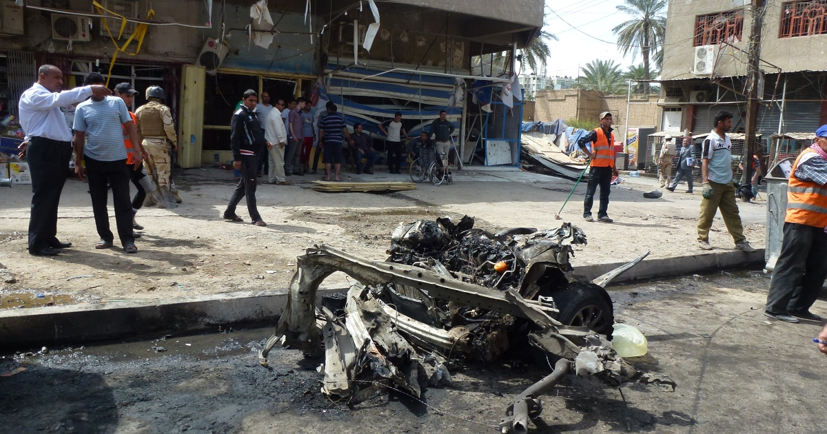 People look at the remains of a car bomb explosion near the fortified 'Green Zone' in the capital of Baghdad, on March 19, 2013. A wave of attacks and explosions in Iraq killed more than 50 people and officials delayed provincial polls, highlighting security concerns on the eve of the 10th anniversary of the US-led invasion.</p>