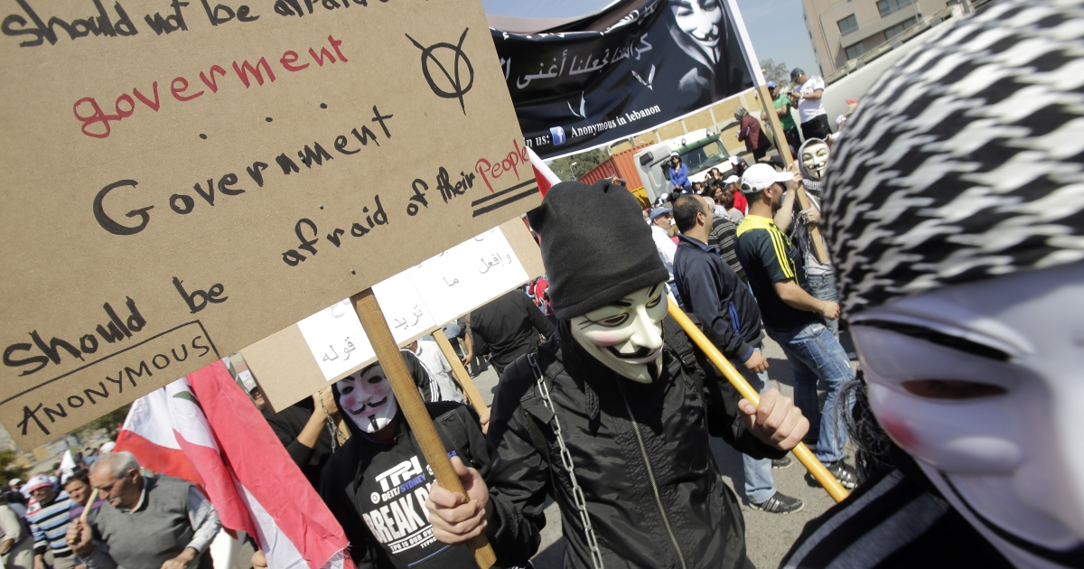 Lebanese protesters wearing a Guy Fawkes mask used by the Anonymous movement carry placards during a protest organized by the public sector employees on March 21, 2013 near the Presidential Palace in Baabda east of the Lebanese capital Beirut, to demand an increase in wages.</p>