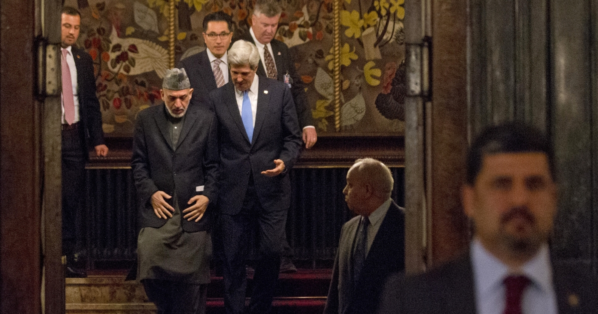 Secretary of State John Kerry and Afghanistan's President Hamid Karzai walk down a flight of stairs at the end of their bilateral meeting before a news conference at the presidential palace in Kabul on March 25, 2013.</p>