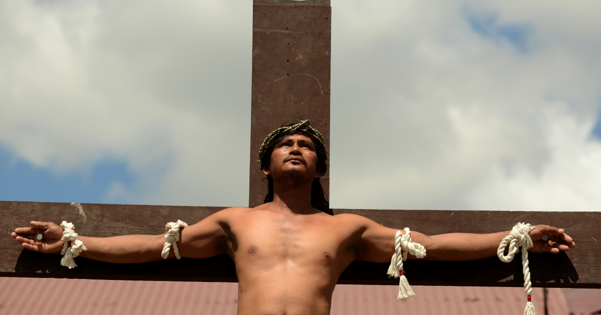 A penintent is nailed to the cross during the reenactment of crucifixion on Good Friday in the village of San Juan, San Fernando City, north of Manila on March 29, 2013.</p>