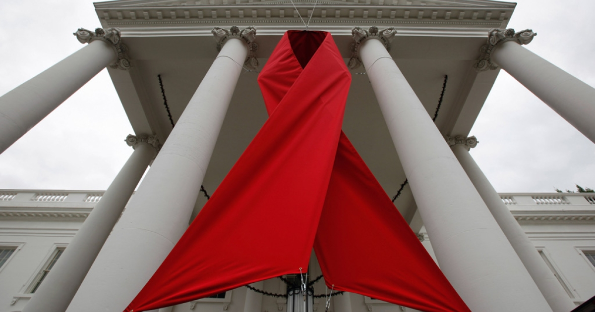 A red ribbon is hung between columns on the north side of the White House to commemorate World AIDS day in Washington, DC.</p>