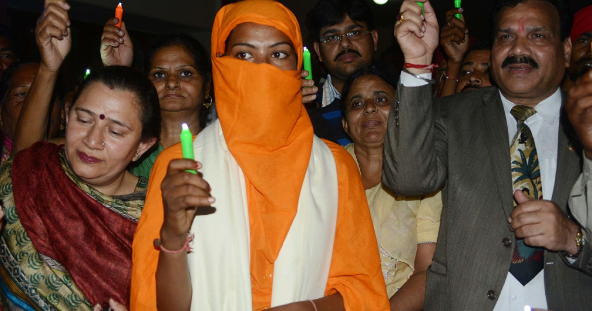 Harbrinder Kaur (C), 22, who was allegedly beaten by police along with members of National Commission for schedule castes, hold candles with others during a vigil on International Women's Day in Amritsar on March 8, 2013.</p>