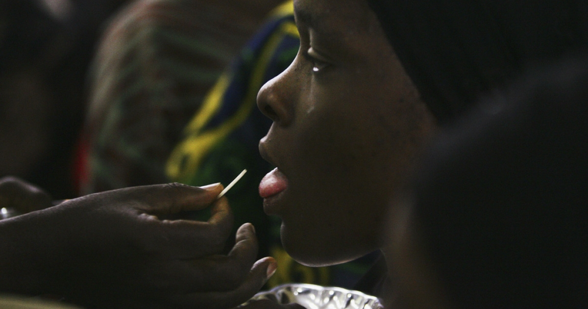 A Nigerian Catholic girl gets communion during morning mass April 12, 2005 in Kano, Nigeria. Kano is part of Nigeria's primarily Muslim north, but devoted Catholic minority participates in frequent Masses in local cathedrals.</p>