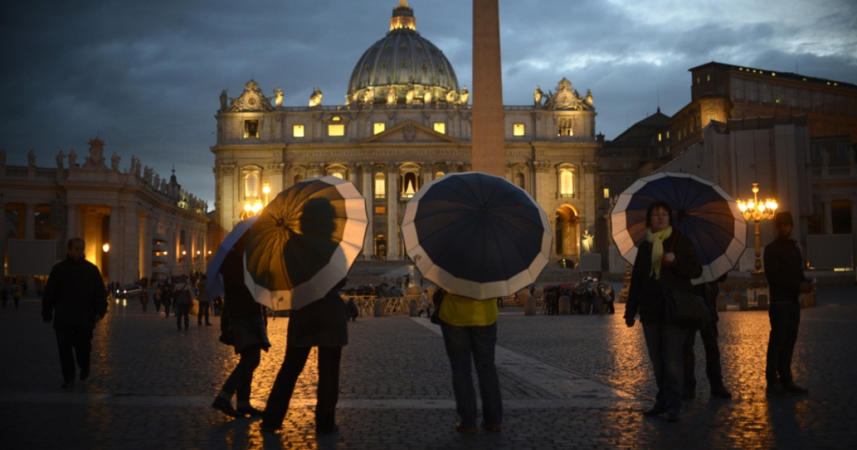 Tourists hold umbrellas as they stand on St Peter's square on March 11, 2013 at the Vatican.</p>