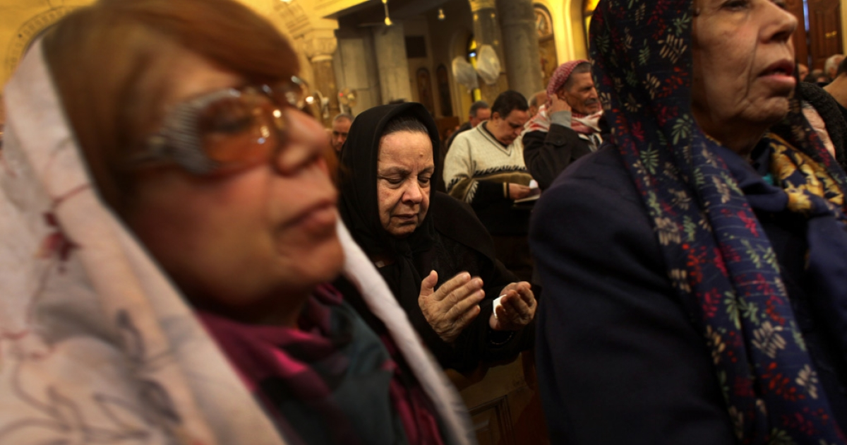 A woman holds her hands together during an early morning prayer service at the Church of the Virgin Mary.</p>