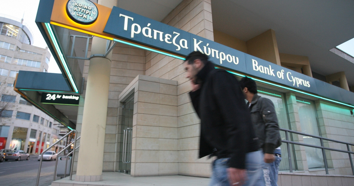 Nicosia, CYPRUS: Two men walk past a Bank of Cyprus branch on Nicosia's Makarios main thoroughfare.</p>