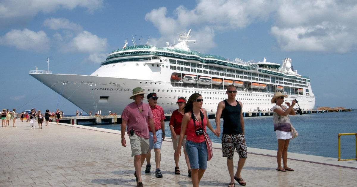 Tourists walk at Cozumel's port, Mexico, after arriving on board of the 'Enchantment of the Seas' cruise ship, on May 27, 2009.</p>
