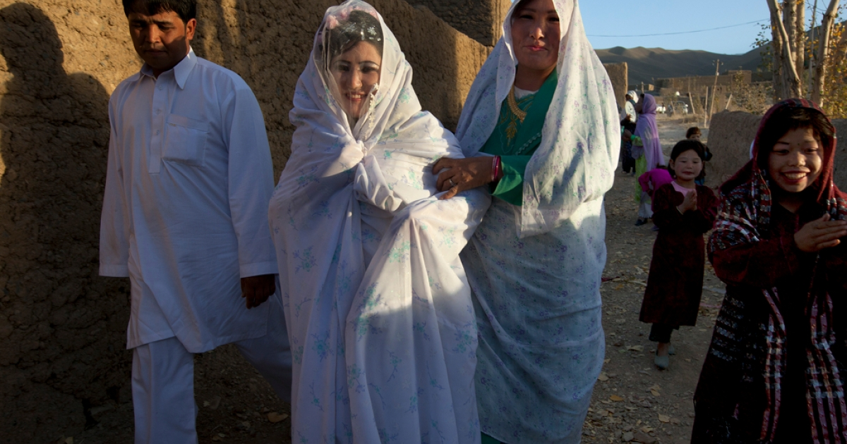 Afghan bride Zahara, 24, is held by the groom Gulam Ali and her sister as they walk to the wedding ceremony held at the family house Oct. 14, 2010 in Bamiyan, Afghanistan.</p>