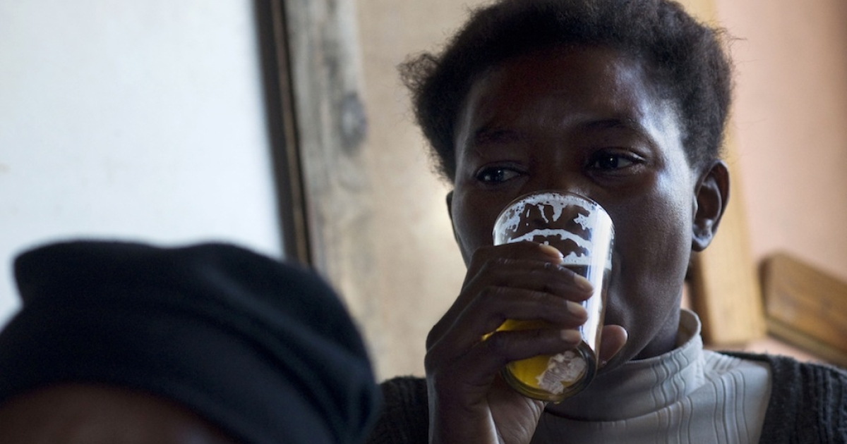 A woman drinks a beer in a 'shebeen', an illegal tavern, usually in someone's home, in Gugulethu, on Feb. 10, 2012, about 15Km from the centre of Cape Town, South Africa.</p>