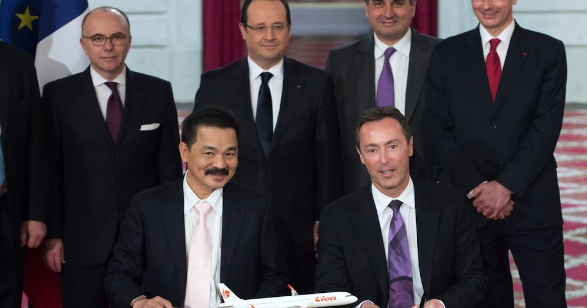Lion Air founder and president director Rusdi Kirana (L) and French CEO of European aerospace giant Airbus Fabrice Bregier (R) pose with France's President Francois Hollande (C, background), after signing a contract during a ceremony at the Elysee presidential palace in Paris March 18, 2013.</p>
