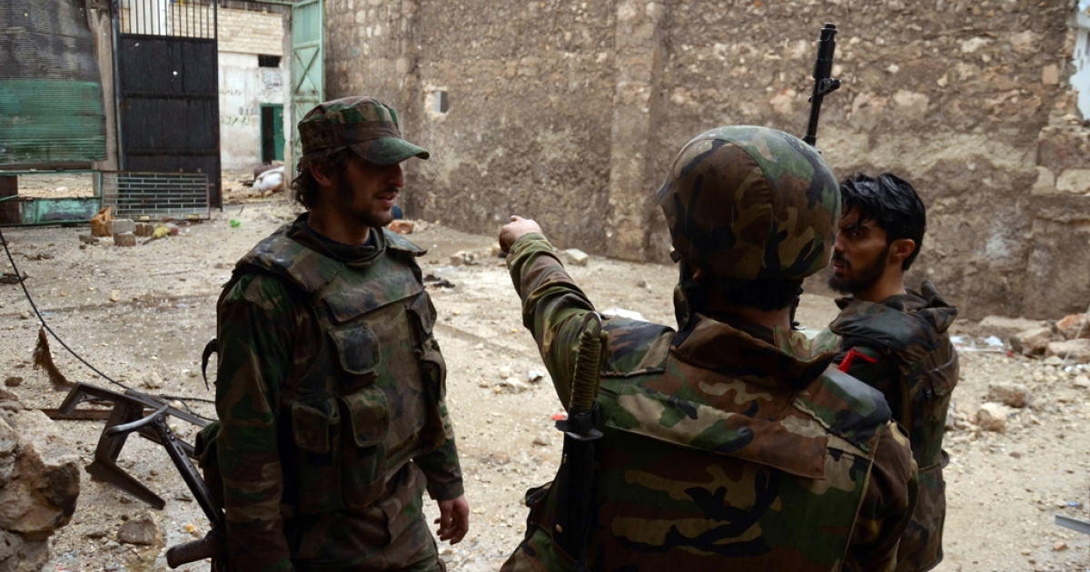 Syrian army soldiers discuss their movements as they clash with opposition fighters in Aleppo on Nov. 11, 2012.</p>